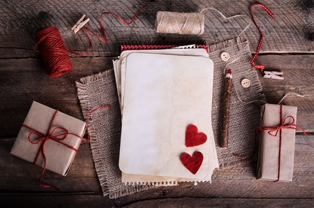 darning needle: Sewing set: fabrics, threads, pins, buttons, tape and handmade hearts on burlap, sackcloth background. Retro design effects.