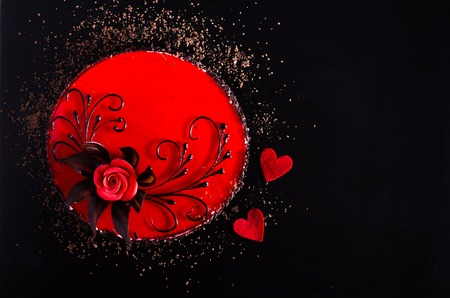 Red Cake with rose, two hearts on black background. Top view. Valentines Day. Stock Photo