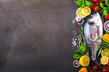 Fresh uncooked fish, dorado, sea bream with lemon, herbs, vegetables and spices on rustic background. Top view. Free space for your text