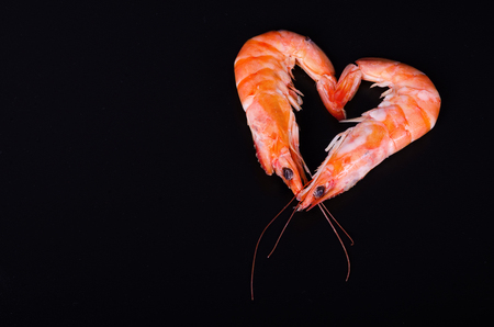 Two shrimps forming a heart in a black background