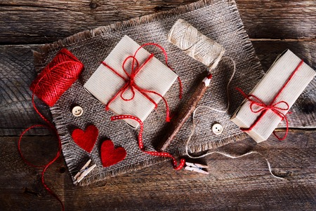 sew tags: Vintage gift boxes with blank gift tag on old wooden background.