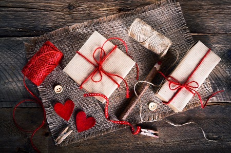 sew tags: Vintage gift box (package) with blank gift tag on old wooden background. Stock Photo