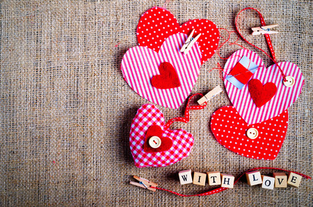 Sewing set: fabrics, threads, pins, buttons, tape and handmade hearts on burlap, sackcloth background. Toned Stock Photo