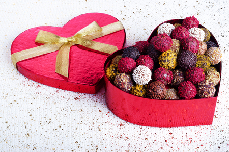 Handmade chocolate candies in red heart shape box with gold bowknot. Copy space.