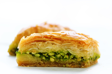 Baklava with pistachios, walnuts and honey on white background. Jewish, turkish, arabic traditional national dessert. Macro. Selective focus. Copy space. Stock Photo