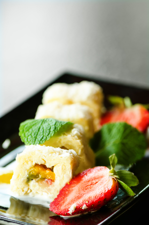 White sweet roll with kiwi, peaches, strawberries, mint. Serverd with almond peach and chocolate sauces on black plate. Sweet dessert for girl, woman, wife