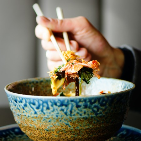 man's: Mans hand holding chopsticks over a plate of Japanese, thai, chinese meal - rice, mushroom, vegetables. Cafe, restaurant. Business lunch. Copy space