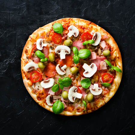Fresh italian pizza with mushrooms, ham, tomatoes, cheese on on black concrete background. Copy space. Homemade with love. Fast delivery. Recipe and menu. Top view. Square.