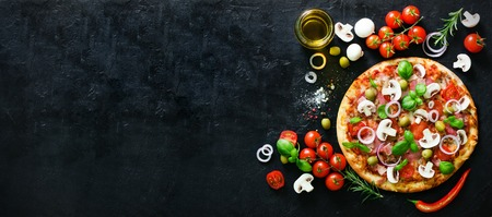 Food ingredients and spices for cooking mushrooms, tomatoes, cheese, onion, oil, pepper, salt, basil, olive and delicious italian pizza on black concrete background. Copyspace. Top view. Banner