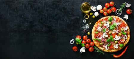 Voedselingrediënten en kruiden voor het koken van champignons, tomaten, kaas, ui, olie, peper, zout, basilicum, olijf en lekkere Italiaanse pizza op zwarte betonnen achtergrond. Copyspace. Bovenaanzicht. banier Stockfoto