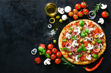 Food ingredients and spices for cooking mushrooms, tomatoes, cheese, onion, oil, pepper, salt, basil, olive and delicious italian pizza on black concrete background. Copyspace. Top view Standard-Bild
