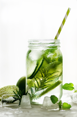 Homemade lime lemonade with cucumber, rosemary and ice, white background. Cold beverage for hot summer day. Copyspace. Banner.