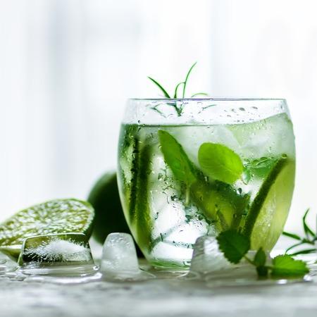 キュウリ、ローズマリーと氷、白い背景と自家製ライム レモネード。夏の暑い日に冷たい飲み物は。Copyspace。