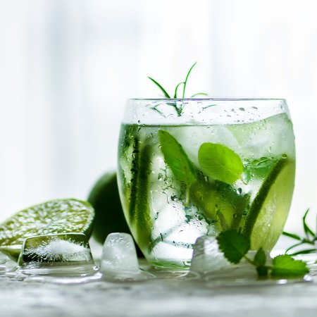 Homemade lime lemonade with cucumber, rosemary and ice, white background. Cold beverage for hot summer day. Copyspace.