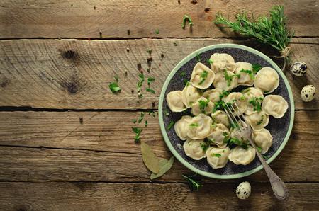 伝統的なロシアのペリメニ、ラビオリ、小麦粉、パセリ、ウズラの卵、コショウ、ローズマリー、月桂樹の葉、スパイスの木製テーブルの上の肉餃 写真素材