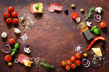Food ingredients and spices for cooking pizza. Mushrooms, tomatoes, cheese, onion, oil, pepper, salt, basil, grater, olive on rustic background. Copyspace. Top view
