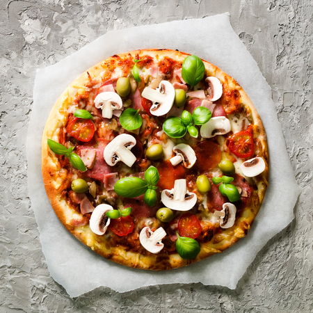 Fresh italian pizza with mushrooms, ham, tomatoes, cheese on on backing paper, grey concrete background. Copy space. Homemade with love. Fast delivery. Recipe and menu. Top view. Stock Photo