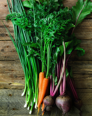 Fresh vegetables - carrots, beetroots, green onion on wooden background. Harvest. Concept of diet, raw, vegetarian meal. Stock Photo