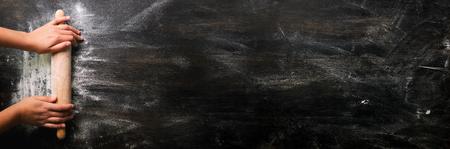 Mädchenhände halten Nudelholz mit Mehl auf dunkler schwarzer Tabelle, backender Hintergrund, Draufsicht, Kopienraum für Ihren Text, meru, Rezept. Banner