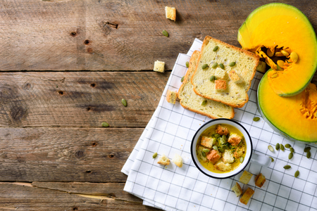 Cup of squash creamy vegetable vegetarian pumpkin carrot soup with crackers and seeds on wooden rustic background, close up, copy space