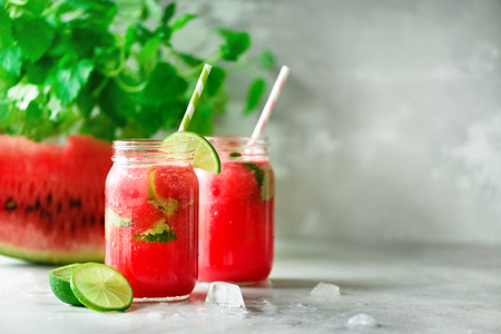 desk: Fresh red watermelon slice and smoothie in glass jar with straw, ice, mint, lime on light background, copy space Stock Photo