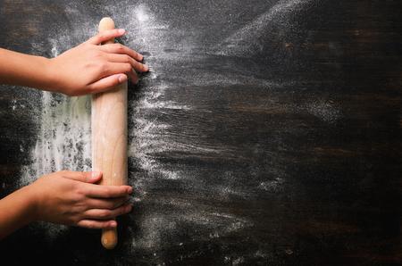 Les mains de la jeune fille gardent le rouleau à pâtisserie avec de la farine sur la table noire foncée, fond de cuisson, vue de dessus, copie espace pour votre texte, meru, recette. Bannière