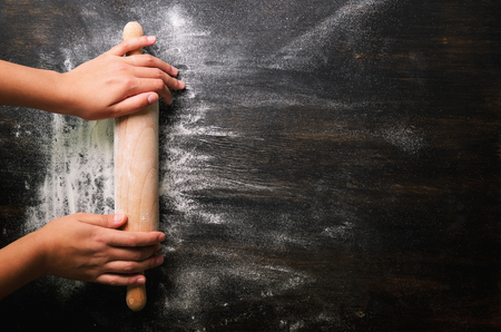 Girl hands keep rolling pin with flour on dark black table, baking background, top view, copy space for your text, meru, recipe. Banner