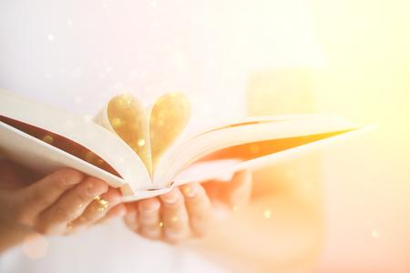 Livro com páginas abertas e forma de coração nas mãos da garota. Copie o espaço. Conceito de amor. Fundo festivo com bokeh e luz solar. Conto de fadas mágico