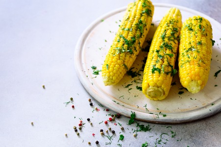 Boiled corn with spices on grey light concrete background. Copy space Stock Photo