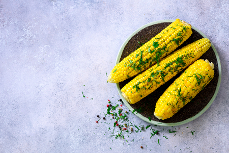 Boiled corn with spices on grey light concrete background. Copy space. Stock Photo