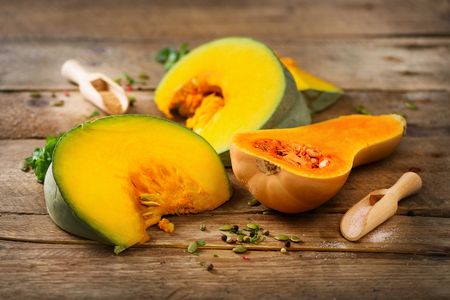 butternut: Cut ripe orange pumpkin with seeds and herbs on rustic wooden background. Vegetarian and raw organic healthy food concept, diet. Top view, copy space Stock Photo