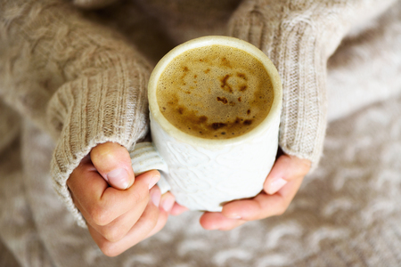 Famale hands holding a cozy ceramic handmade mug with coffe. Winter and Christmas home time concept. Lifestyle. Copy space