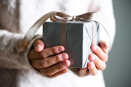 Vrouwelijke handen met geschenkdoos. Ruimte kopiëren. Kerst, houw jaar, verjaardag concept Stockfoto