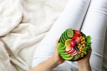 Girl holds in hands vegan, detox raw buddha bowl with avocado, quinoa, cucumber, radish, salad, lemon, cherry tomatoes, chickpea, chia seeds on textile background, copy space, overhead