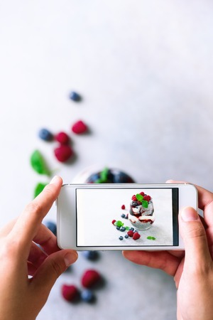 Girl is taking photos of breakfast, chia pudding with berries to mobile phone. Social media concept. Copy space, top view Reklamní fotografie - 89698409