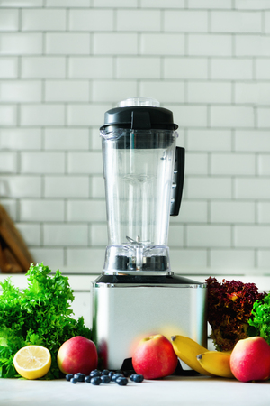 Woman blending lettuce leaves, spinach, aplles, berries, bananas. Homemade healthy green smoothie. White kitchen design