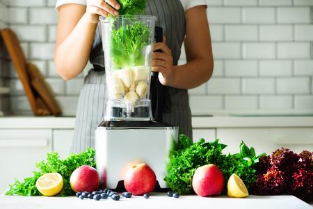 양상추 잎, 시금치, aplles, 딸기, 바나나를 혼합하는 여자. 수 제 건강 한 녹색 스무디입니다. 화이트 주방 디자인