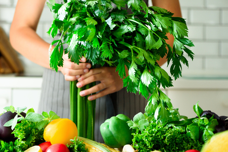 Woman hands holding fresh organic celery. vegetables, onion, tomatoes, corn, bell pepper, spinach, lettuce leaves. Clean eating, detox concept