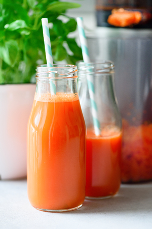 Woman making fresh drink. Juicer and carrot juice. Fruits in background. Clean eating, detox concept Stock Photo