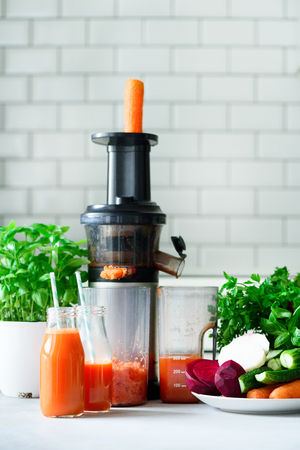Woman makinf fresh drink. Juicer and carrot juice. Fruits in background. Clean eating, detox concept Stock Photo