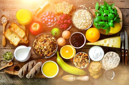 Healthy breakfast ingredients, food frame. Granola, egg, nuts, fruits, berries, toast, milk, yogurt, orange juice, cheese, banana, apple on wooden rustic background, top view, copy space