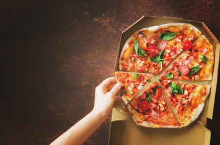 Feminino mão tomando fatia de pizza fresca da caixa de entrega. Vista superior, fundo escuro. Comida não saudável. Manhã ensolarada com a luz solar. Tons pastel