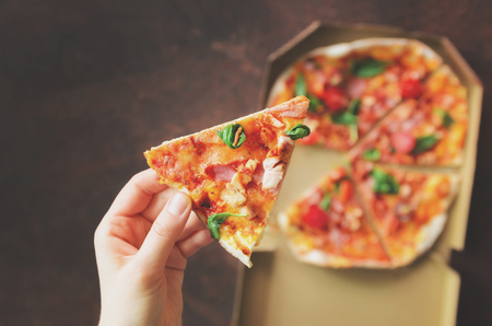 Female hand taking slice of fresh pizza from delivery box. Top view, dark background. Junk food. Sunny morning with sunlight. Toned pastel color