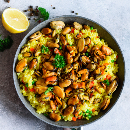 Traditional spanish seafood paella in pan rice, peas, shrimps, mussels, squid on light grey concrete background. Top view, copyspace.