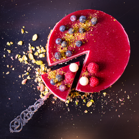 Delicious raspberry cake with fresh strawberries, raspberries, blueberry, currants and pistachios on vintage background. Copy space. Banner