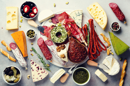 Cutting board with cold smoked meat, prosciutto, salami, assortment of cheeses, bread sticks, capers, olives on grey stone background. Cheese and meat appetizer. Top view, copy space, flat lay.