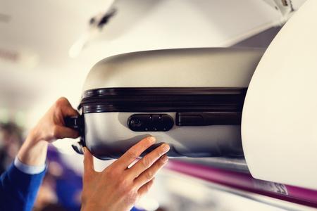 Maletero con maletas en avión. Las manos se quitan el equipaje de mano. El pasajero colocó la bolsa de cabina en el estante superior