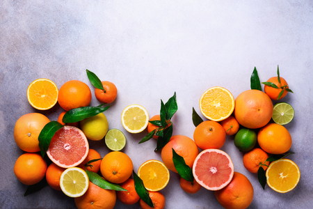 Citrus fruits background. Assorted fresh citrus fruits with leaves. Orange, grapefruit, lemon, lime, tangerine. Top view 写真素材