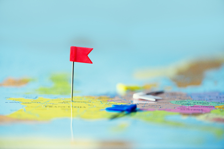 Red flag, pushpin, thumbtack pinned on map of europe. Copy space, travel concept.