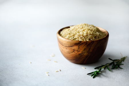 Raw organic brown rice in wooden bowl and rosemary on light concrete background. Food ingredients. Copy space Stock Photo